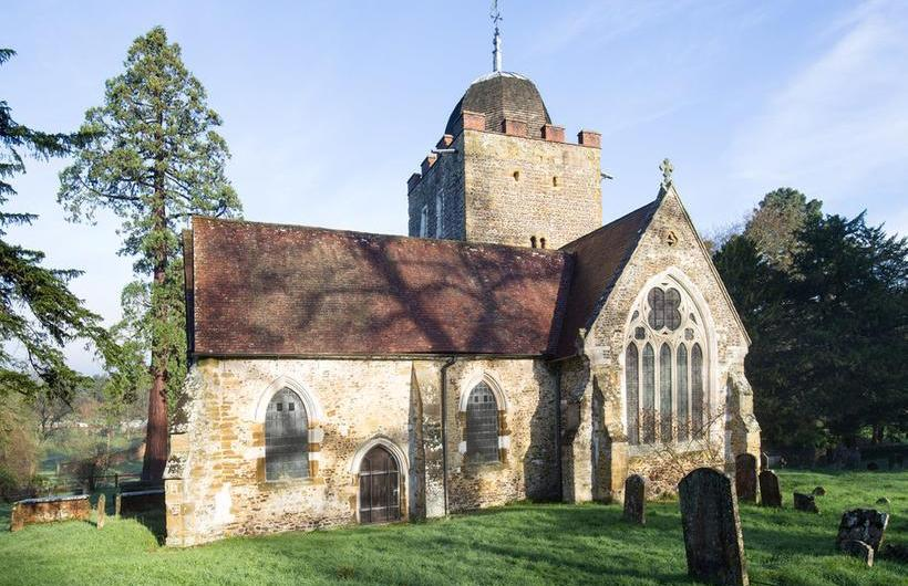 Sunlit image of the exterior of St Peter and St Paul's Church, Albury, Surrey